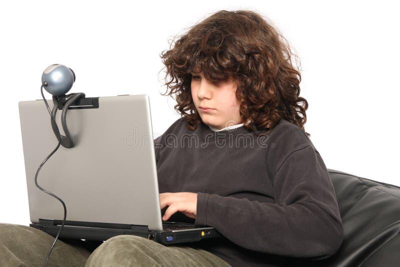 Menino que usa o portátil e a câmara web imagens de stock royalty free