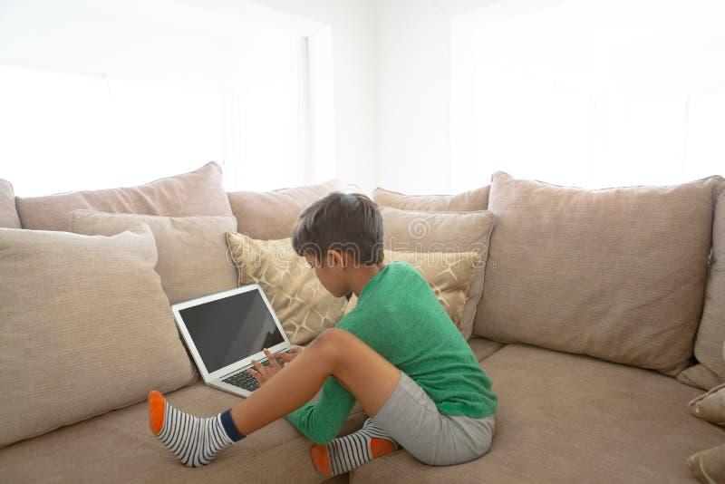 Menino que usa o portátil no sofá em casa imagem de stock