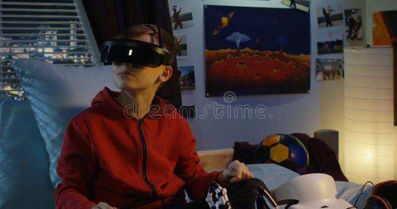 Menino que usa uns auriculares da realidade virtual em casa imagens de stock royalty free