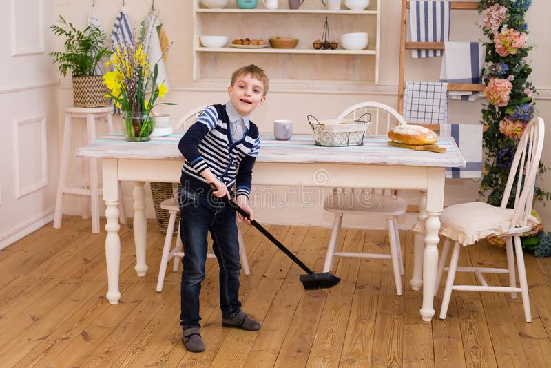 Menino que varre o assoalho na cozinha O menino bonito ajuda pais imagem de stock