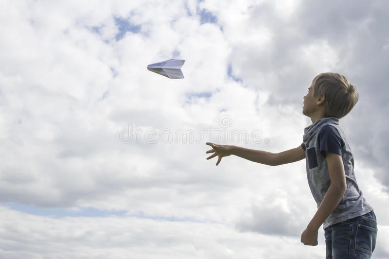 Menino que voa um plano de papel contra o céu azul imagem de stock