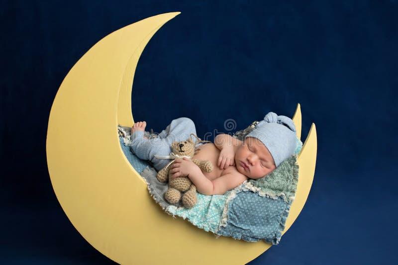 Menino recém-nascido que dorme na lua com Teddy Bear imagem de stock