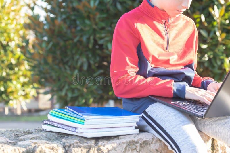 Menino sério do adolescente com o portátil e os livros de texto que fazem trabalhos de casa e que preparam-se para um exame no pa imagens de stock royalty free