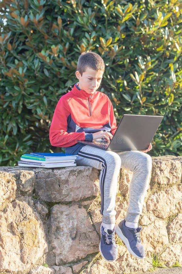 Menino sério do adolescente com o portátil e os livros de texto que fazem trabalhos de casa e que preparam-se para um exame no pa imagem de stock