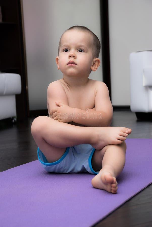 Menino sério que senta-se em uma esteira da ioga fotografia de stock