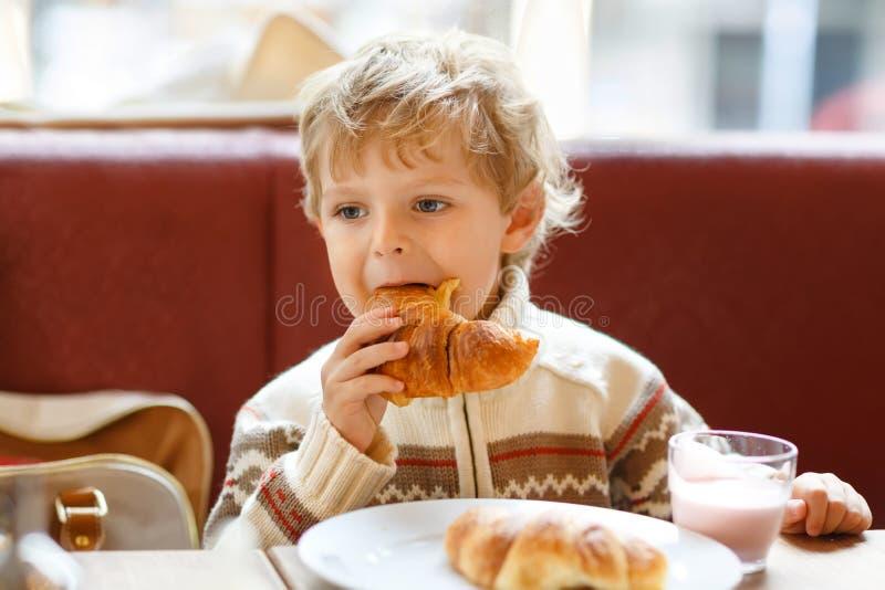 Menino saudável bonito da criança que come o croissant e que bebe o milk shake da morango no café Criança feliz que come o café d foto de stock royalty free