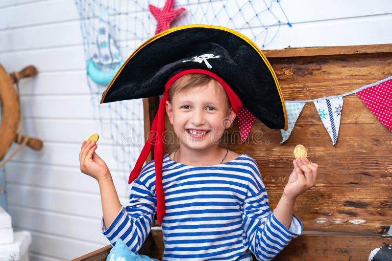 Menino sob a forma dos piratas no leme imagens de stock