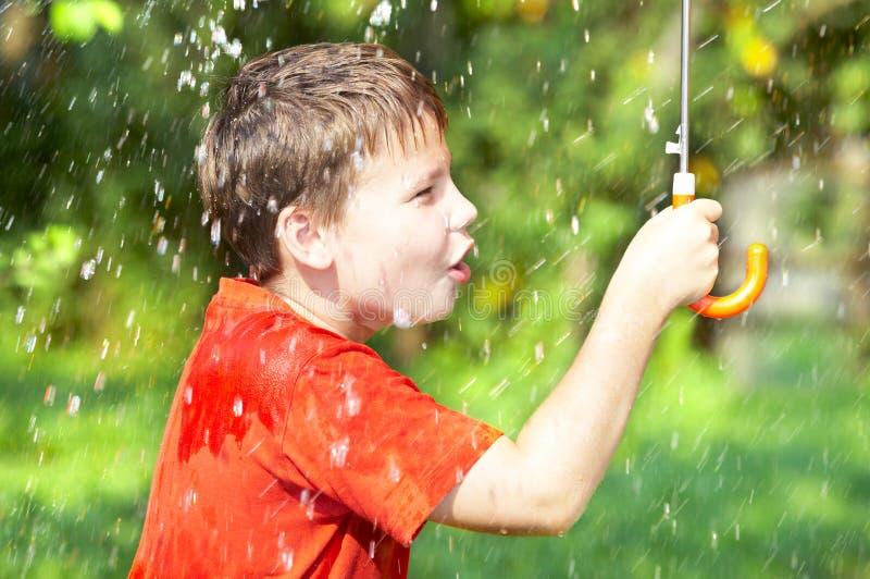 Menino sob um guarda-chuva durante uma chuva fotos de stock royalty free