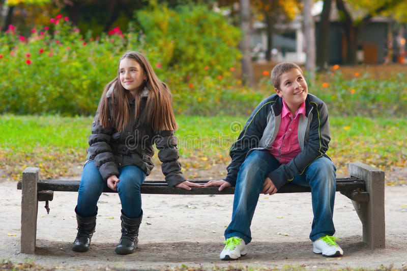 Menino tímido e a menina que senta-se no parque fotografia de stock royalty free