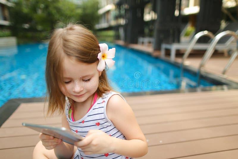 Menino tomando selfie em tablet sentado perto da piscina fotos de stock
