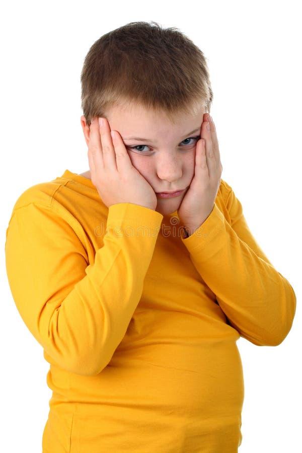 Menino triste dos anos de idade 10 que mantem seus mordentes isolados imagem de stock royalty free