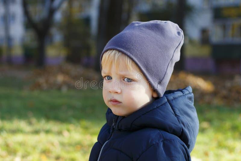 Menino triste no chapéu exterior Tiro do outono Retrato bonito do perfil da criança Copie o espaço imagens de stock royalty free