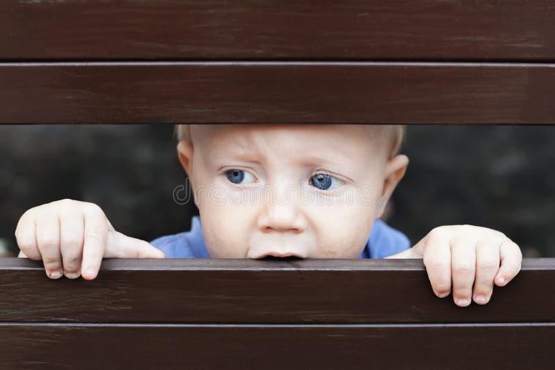 Menino triste pequeno que olha para fora através da cerca foto de stock royalty free