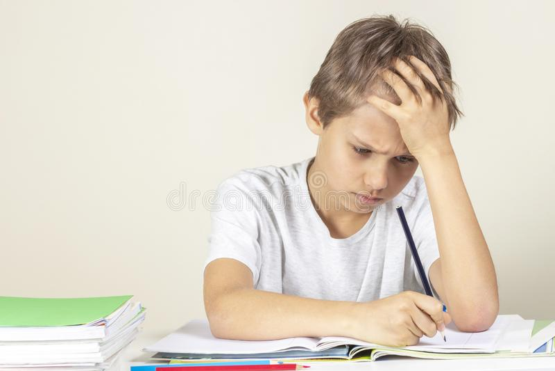 Menino triste que faz trabalhos de casa Educa??o, escola, conceito das dificuldades de aprendizagem imagens de stock royalty free