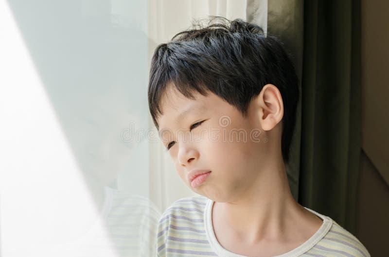 Menino triste que olha fora da janela fotografia de stock