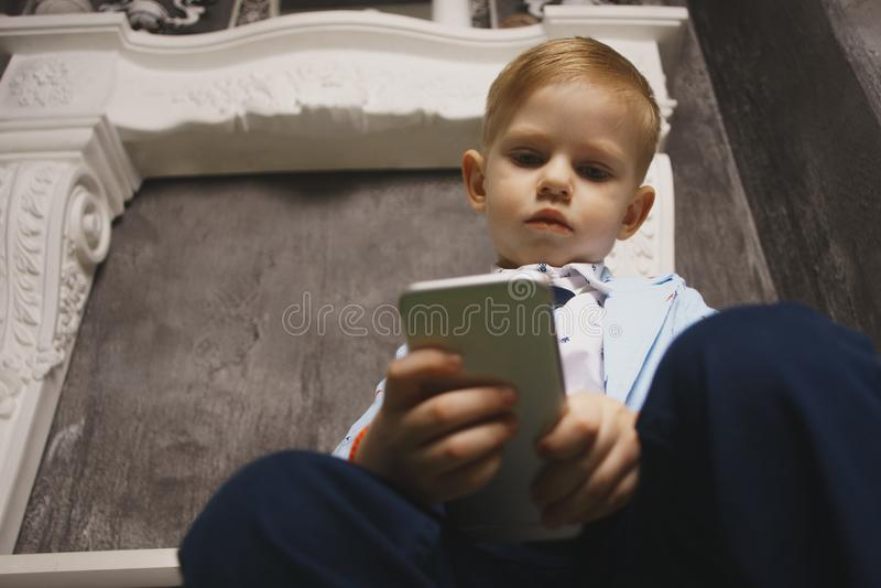 Menino triste que olha o telefone celular com mão na cabeça fotografia de stock royalty free