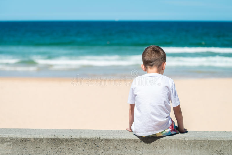 Menino triste que senta-se na praia imagens de stock royalty free
