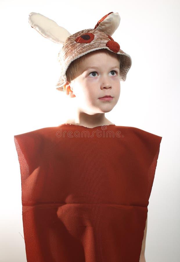 Menino vestido como o coelho pequeno no fundo branco imagem de stock