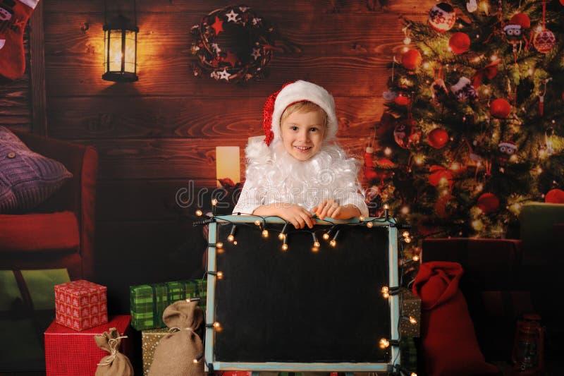 Menino vestido no Natal de Papai Noel imagem de stock