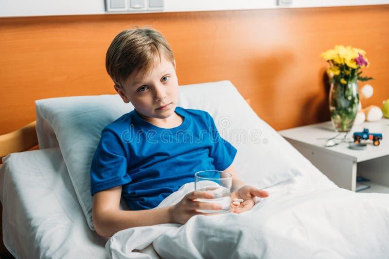 Menino virado que guarda o vidro da água e das medicinas na cama de hospital foto de stock royalty free