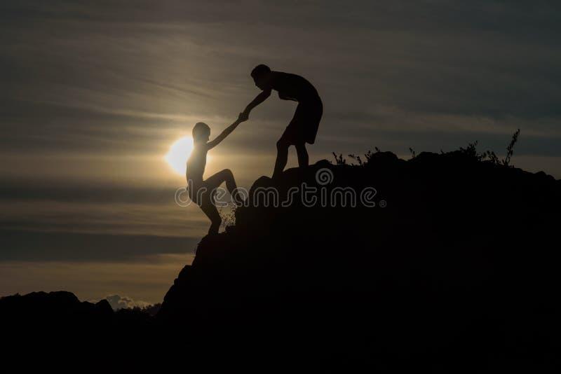 Meninos ajudados a puxar junto a escalada foto de stock