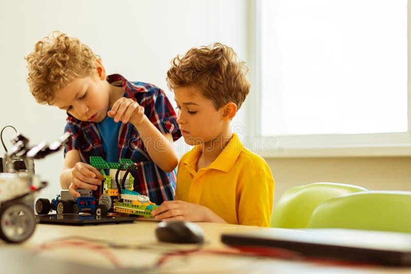 Meninos bonitos agradáveis que trabalham junto durante a classe fotos de stock royalty free