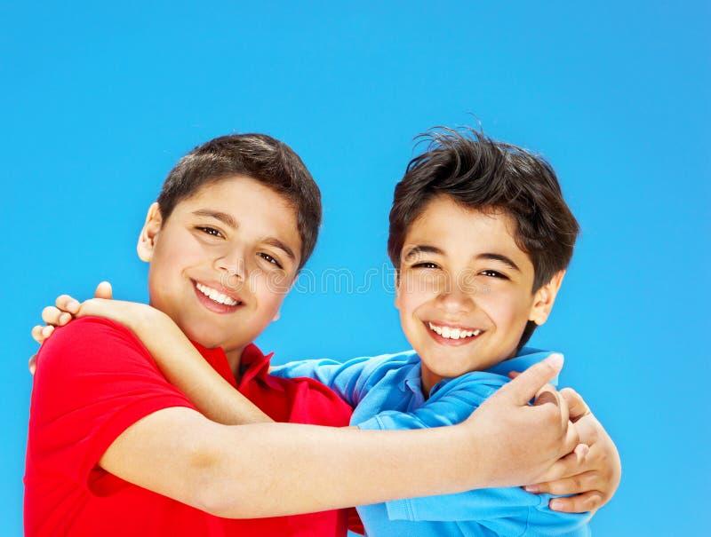 Meninos bonitos felizes sobre o céu azul imagens de stock