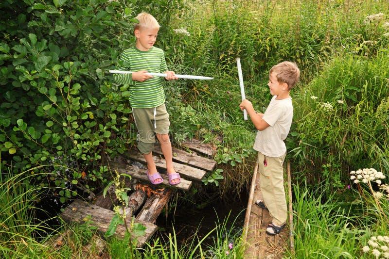 Meninos com varas que lutam para o divertimento em pontes