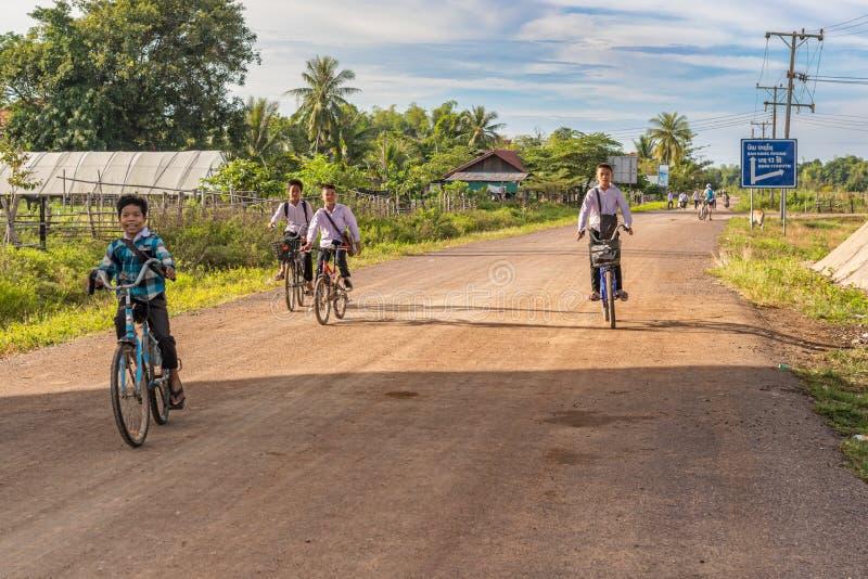 Meninos de escola em bicicletas em Muang Khong, Laos fotografia de stock