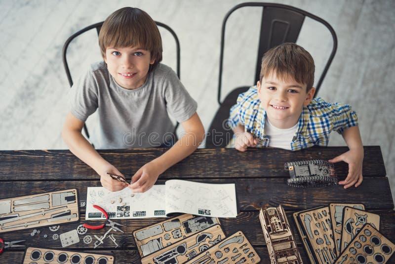 Meninos de sorriso que colocam as cabeças ao sentar-se na tabela fotografia de stock