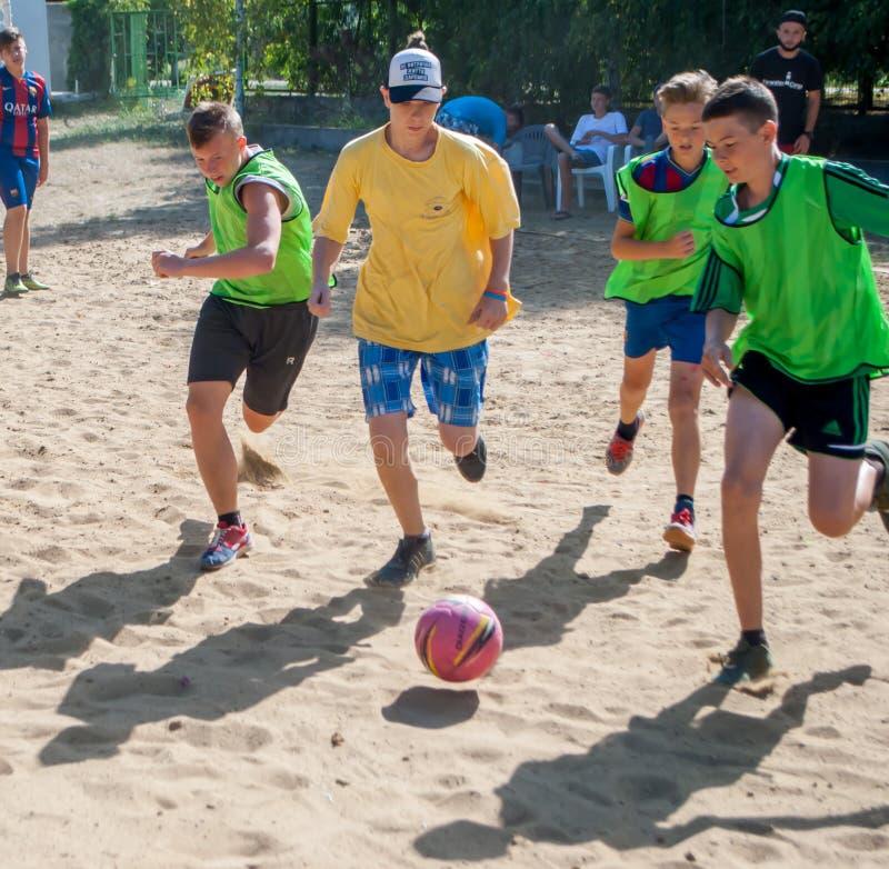 Meninos do futebol que correm para a bola em um campo arenoso em um acampamento de verão foto de stock royalty free