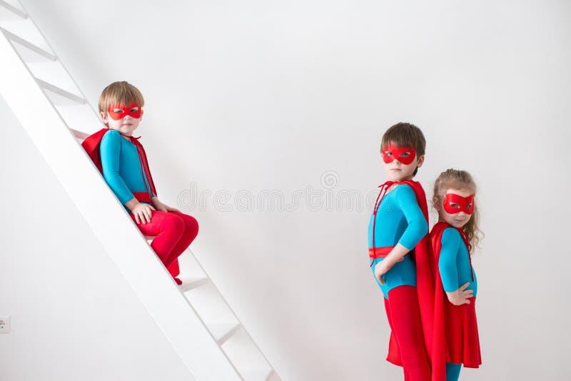 Meninos e menina que jogam o super-herói imagem de stock
