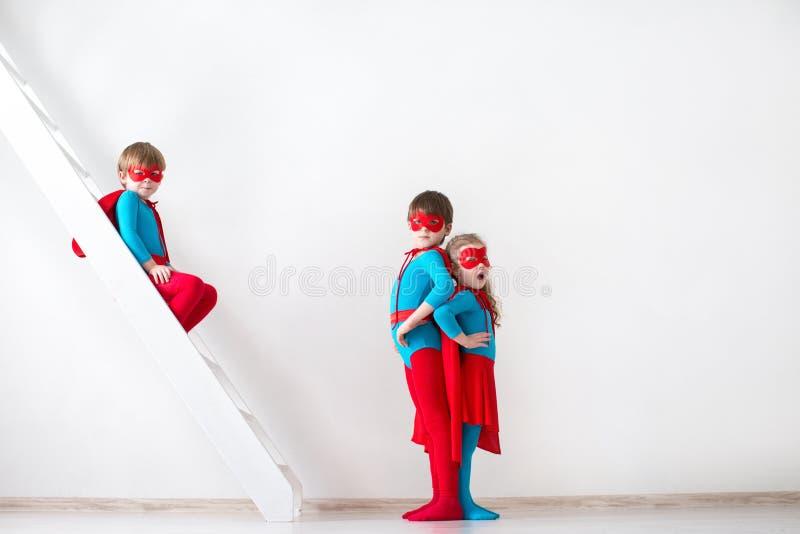 Meninos e menina que jogam o super-herói imagem de stock royalty free