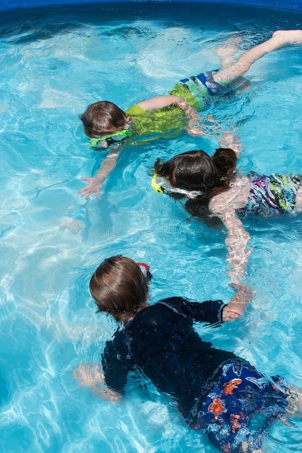 Meninos e menina que mantêm as mãos subaquáticas na piscina fotos de stock royalty free