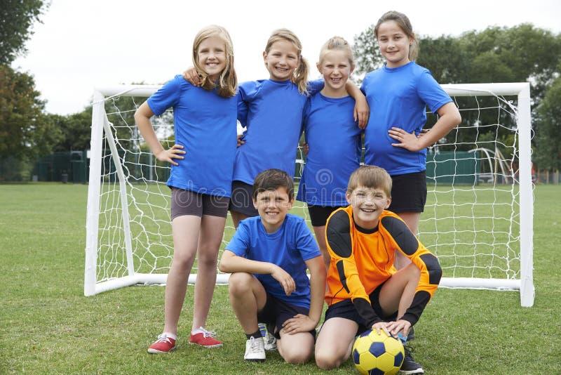 Meninos e meninas na equipe de futebol da escola primária imagem de stock royalty free