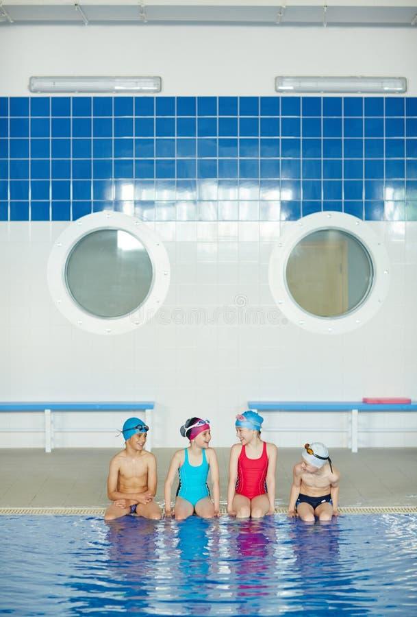 Meninos e meninas na prática da natação imagem de stock