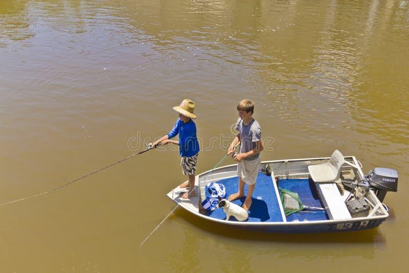 Meninos e pesca do cão no barco no rio inundado. fotografia de stock royalty free