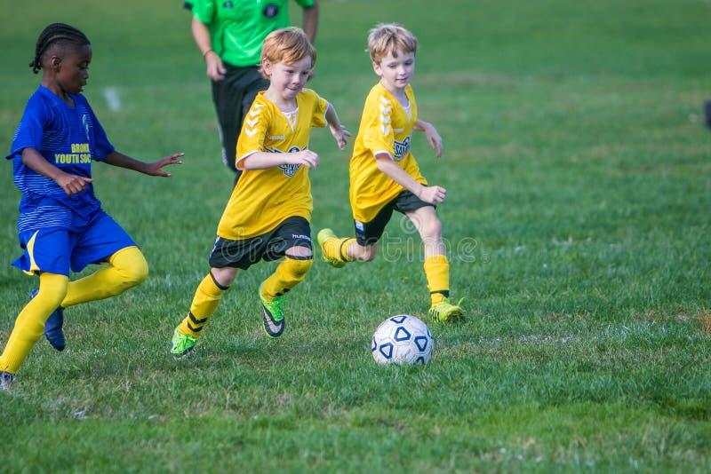Meninos em duas equipes que jogam um jogo de futebol foto de stock