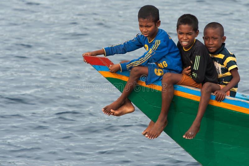 Meninos em um barco de pesca no passo de Alor, Indonésia fotos de stock