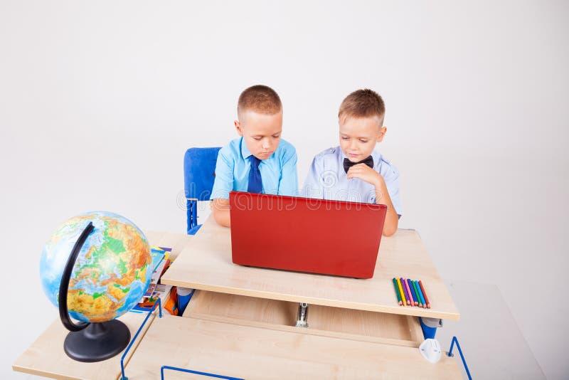 Meninos em um computador nas lições da escola do Internet fotografia de stock royalty free