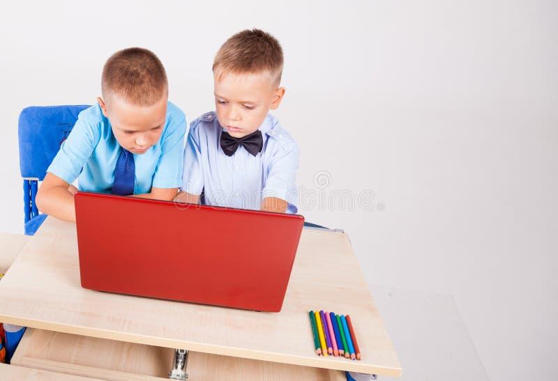 Meninos em um computador nas lições da escola do Internet fotos de stock