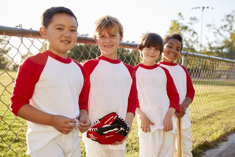Meninos em uma equipa de beisebol com luva e no bastão que olha à câmera fotografia de stock