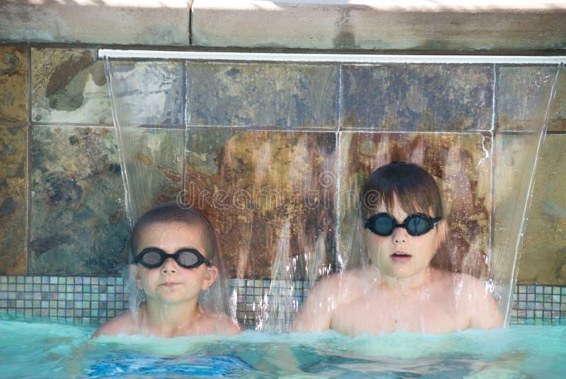 Meninos em uma piscina fotografia de stock