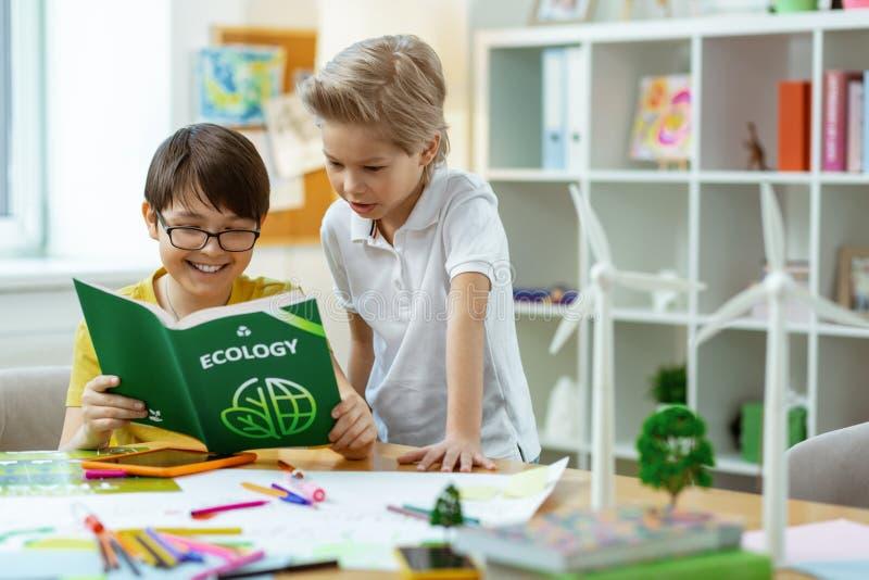 Meninos espertos curiosos observando o livro educativo sobre a ecologia foto de stock royalty free