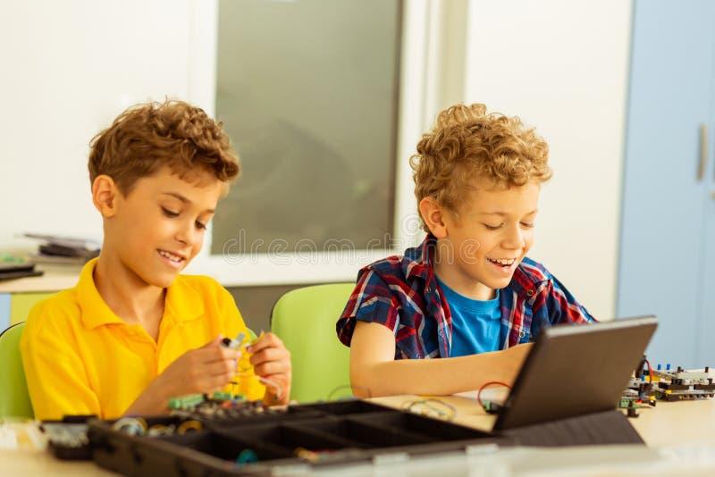 Meninos felizes deleitados que estão sendo contratados na atividade fotos de stock royalty free