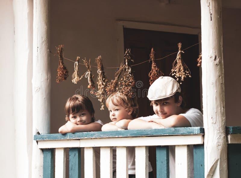 Meninos felizes no patamar de uma casa velha fotos de stock royalty free