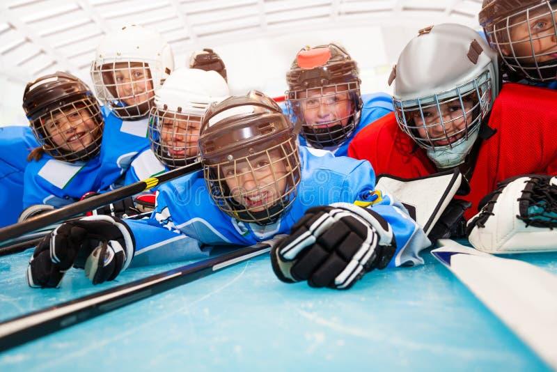 Meninos felizes no uniforme do hóquei que coloca na pista de gelo fotografia de stock