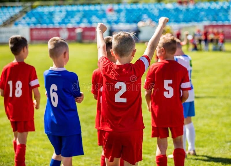 Meninos felizes que ganham o fósforo de futebol Equipa de futebol bem sucedida nova do futebol imagens de stock royalty free