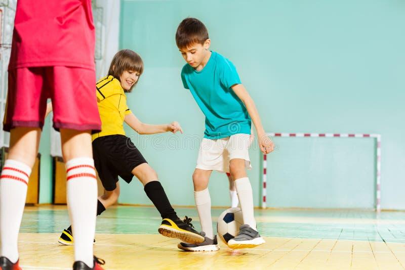 Meninos felizes que jogam o futebol no salão de esportes da escola imagem de stock