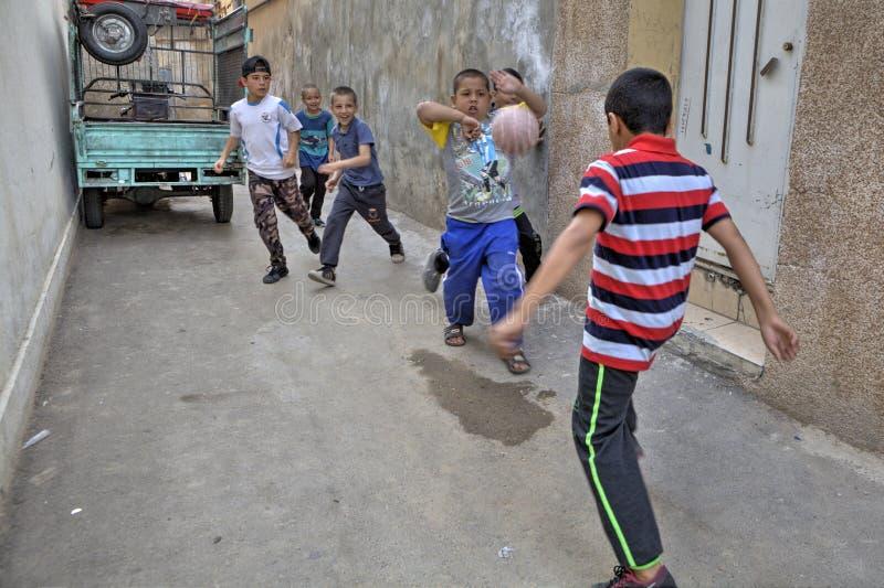 Meninos iranianos da rua que jogam o futebol na jarda, Shiraz, Irã fotos de stock